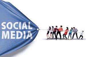 Portrait of business team pulling together a banner of social media