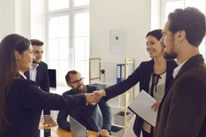 Happy business people and shaking hands
