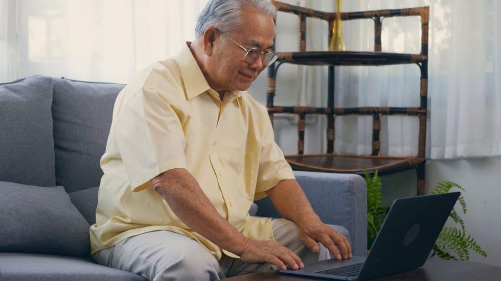 Senior man dressed wear eyeglasses sitting on sofa